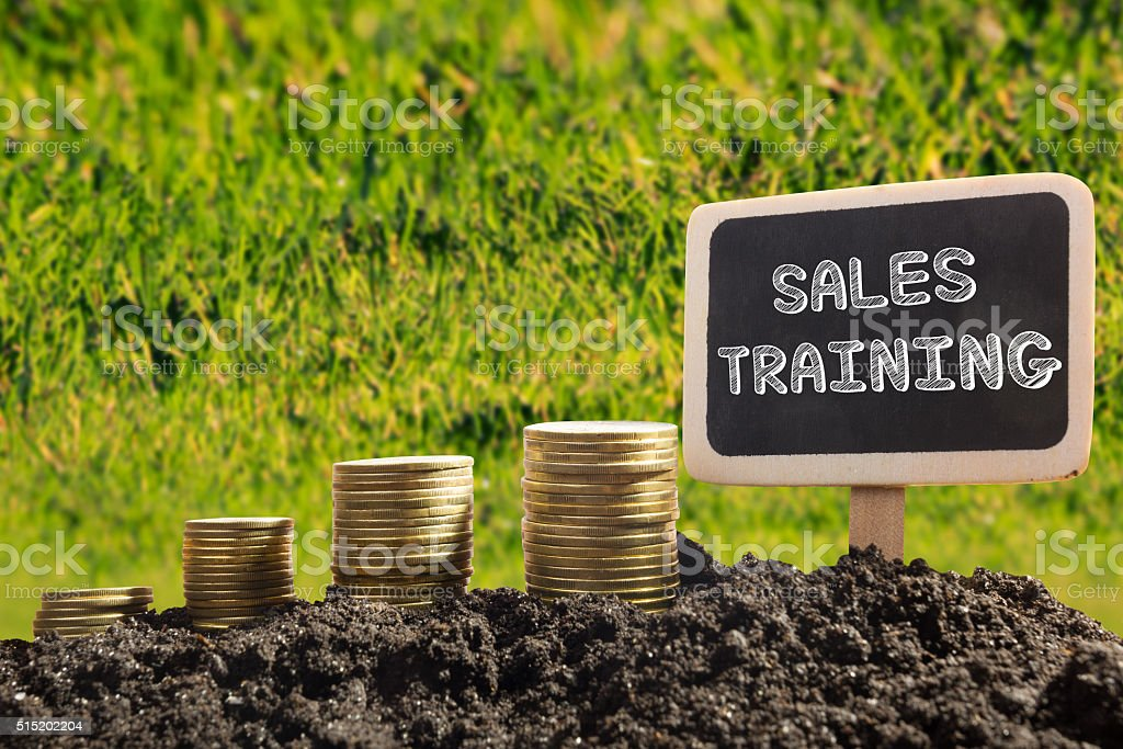 Sales training. Financial opportunity concept. Golden coins in soil Chalkboard stock photo