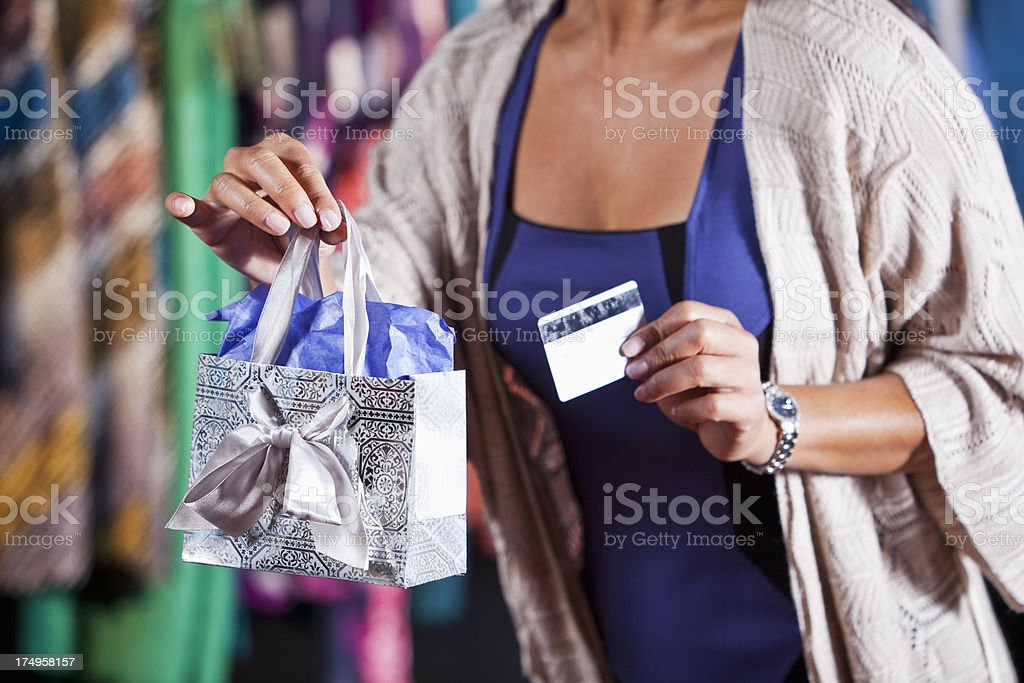 Sales woman holding shopping bag and payment card royalty-free stock photo