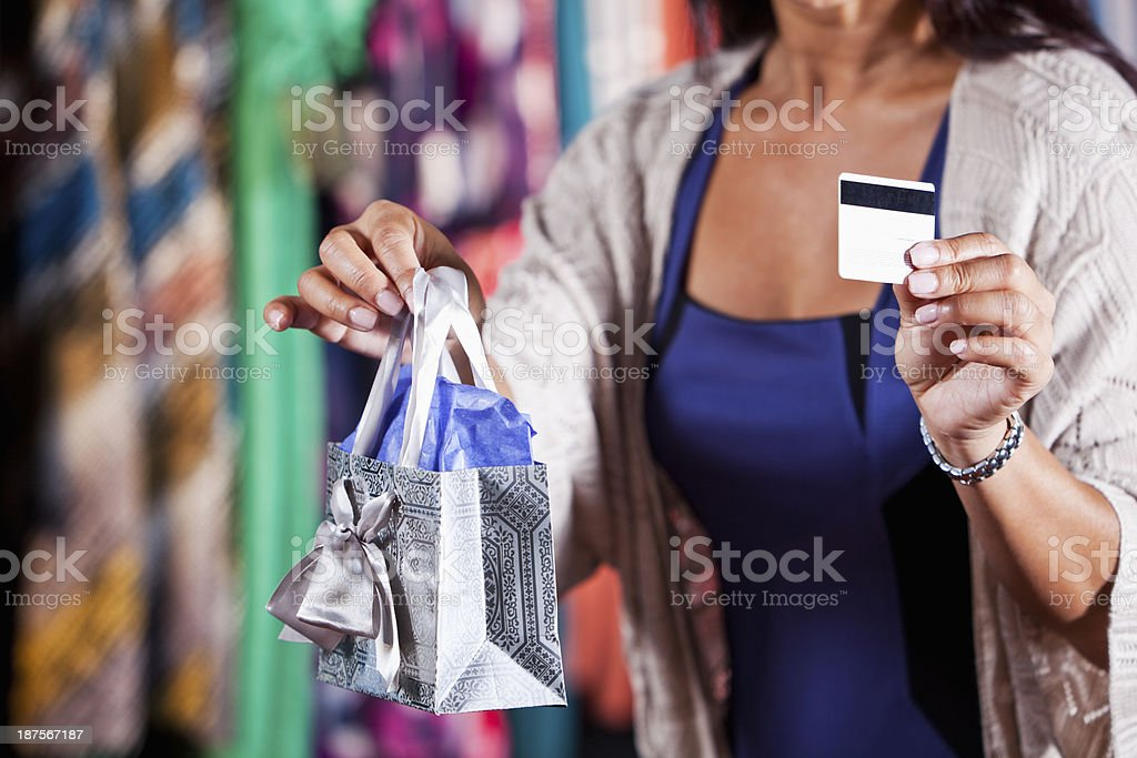 Sales woman holding shopping bag and payment card stock photo