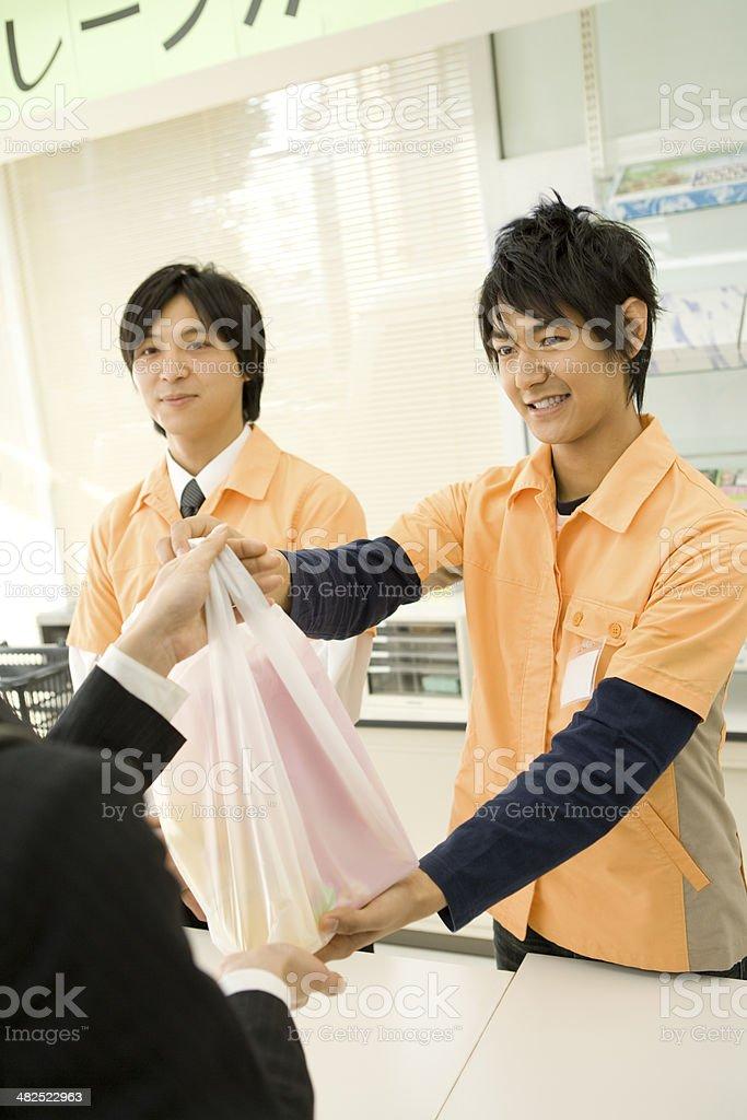 Salesclerk handing goods royalty-free stock photo