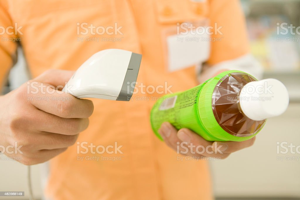 Salesclerk of convenience store scanning bar code stock photo