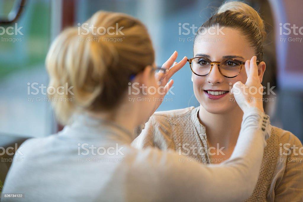 Salesgirl Assisting Customer To In Wearing Glasses stock photo