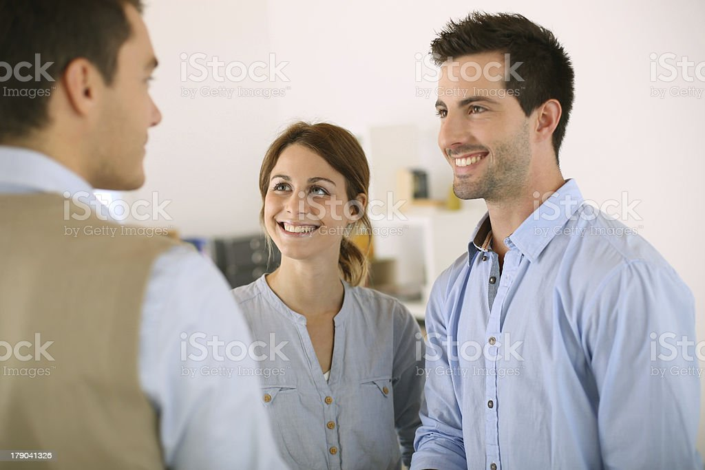 Salesman and couple standing in office royalty-free stock photo