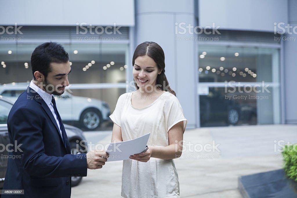 Salesman and woman at car dealership stock photo