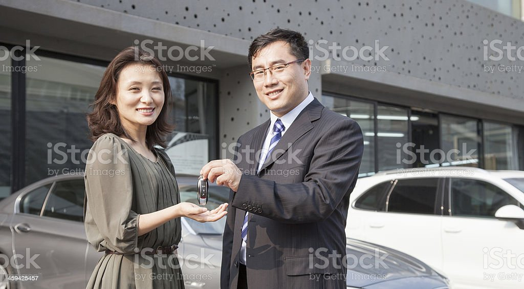 Salesman handing keys to customer stock photo