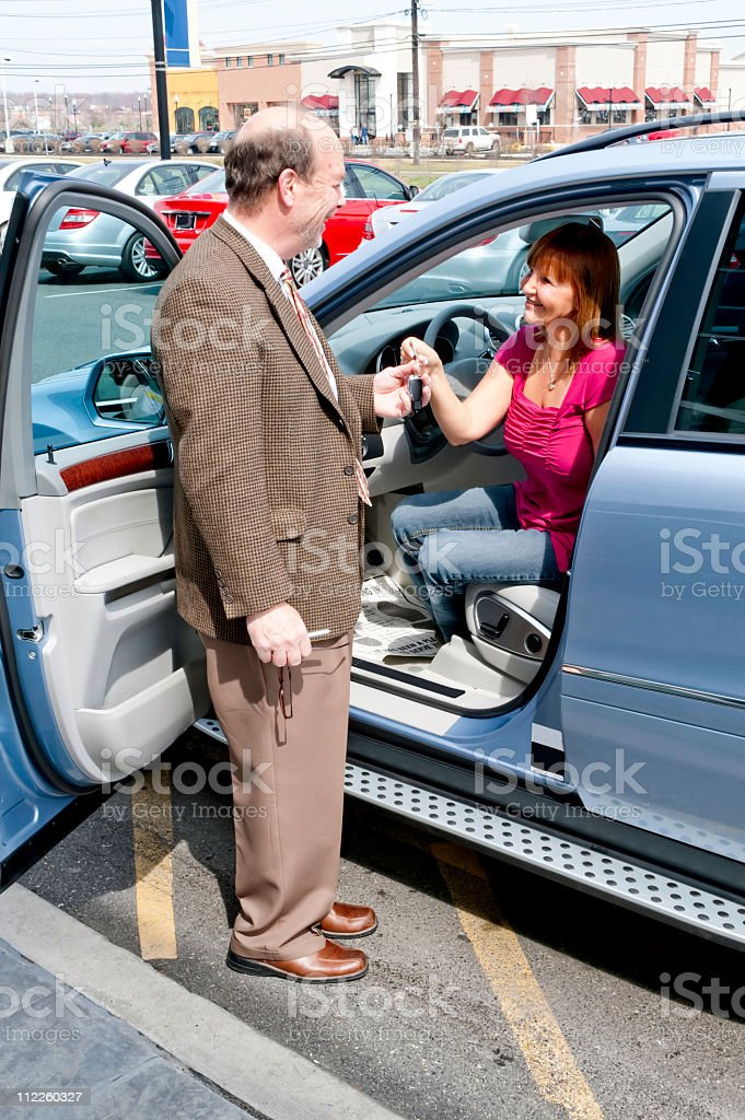 salesman handing keys to new car royalty-free stock photo