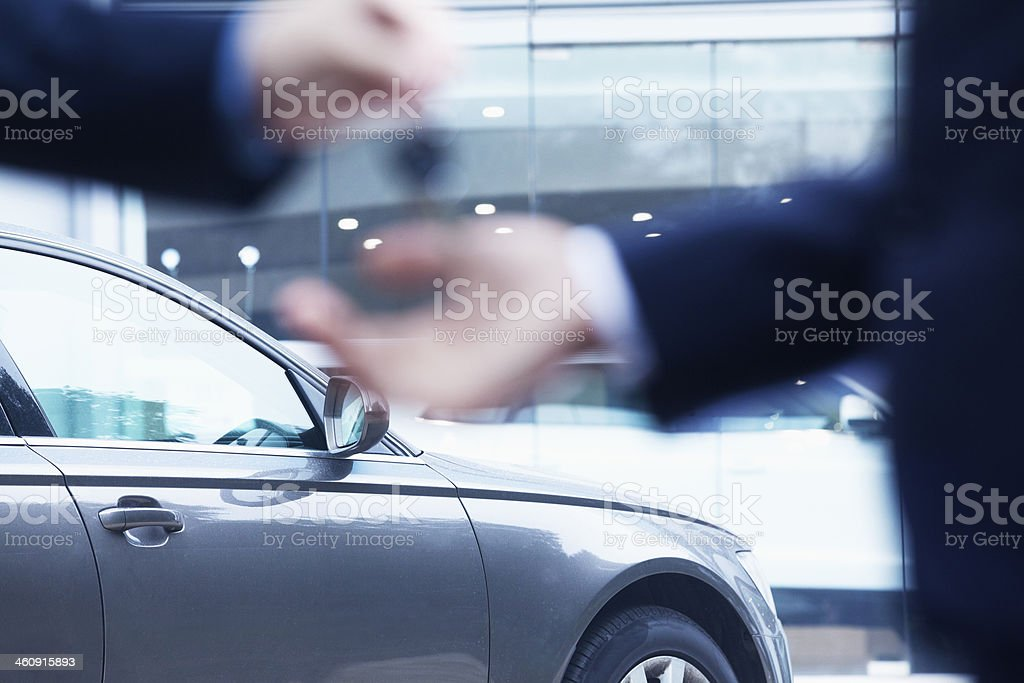 Salesman handing over keys for new car to young businessman stock photo