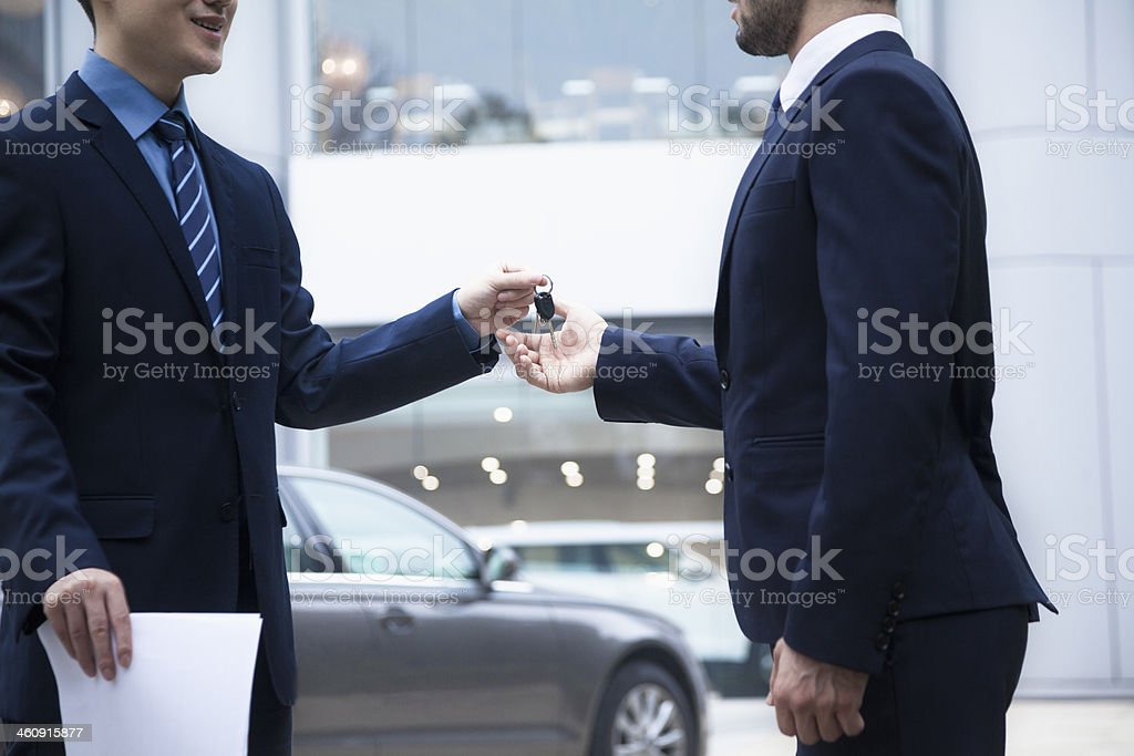 Salesman handing over the keys for new car to businessman stock photo