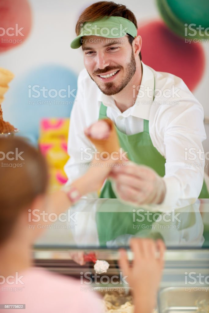 Salesman in confectionery provides ice cream to girl stock photo