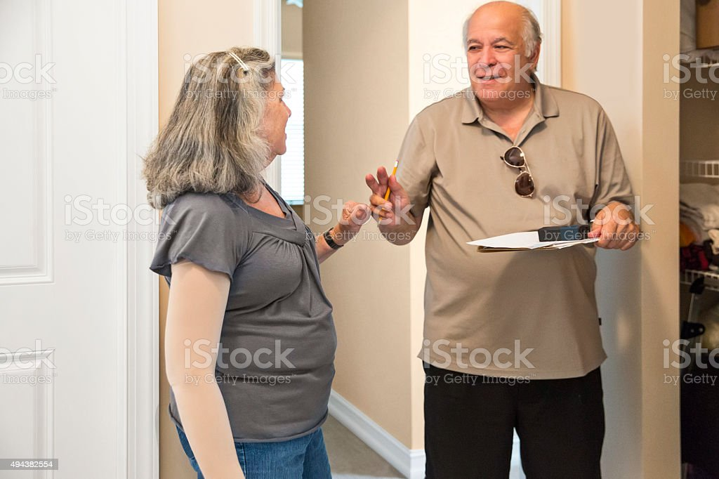 Salesman meeting with client for custom closet installation in home stock photo
