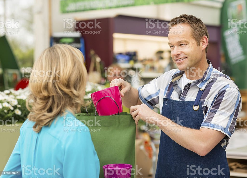 Salesman Putting Product In Shopping Bag royalty-free stock photo