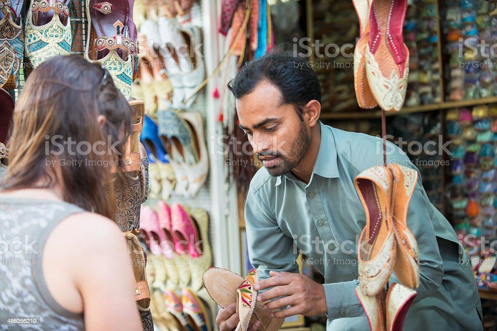 Salesman Showing Shoes to Woman Shopping at Souk, Dubai, UAE stock photo