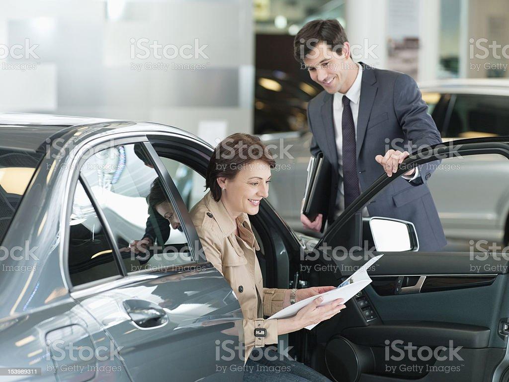 Salesman watching woman look at brochure in car dealership showroom royalty-free stock photo