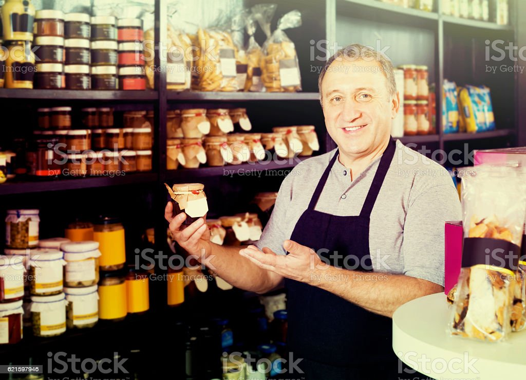salesman working in delicatessen section of ordinary grocery stock photo