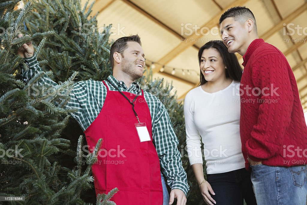 Salesperson assisting couple purchasing Christmas tree royalty-free stock photo