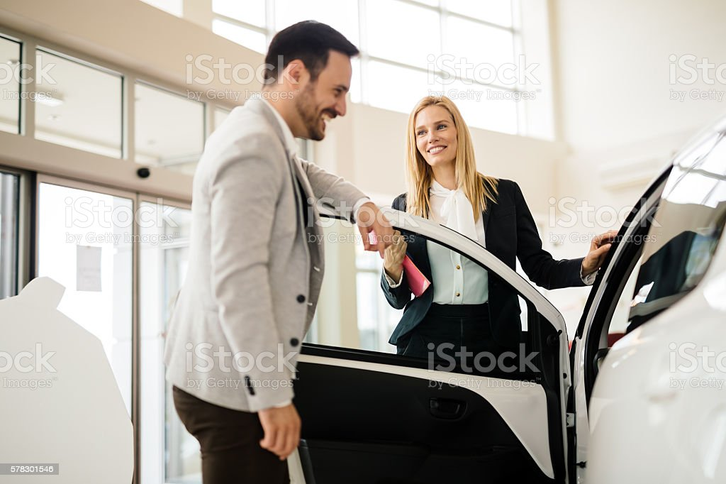Salesperson showing vehicle to potential customer stock photo