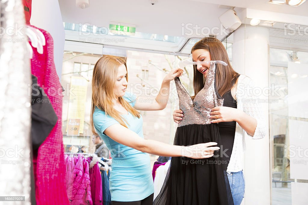 salesperson talking to customers in fashion store stock photo