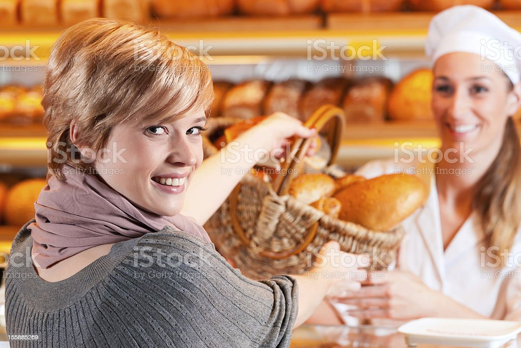 Salesperson with female customer in bakery royalty-free stock photo