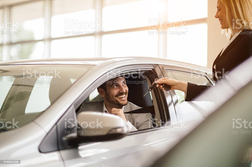 Salesperson working at car dealership stock photo