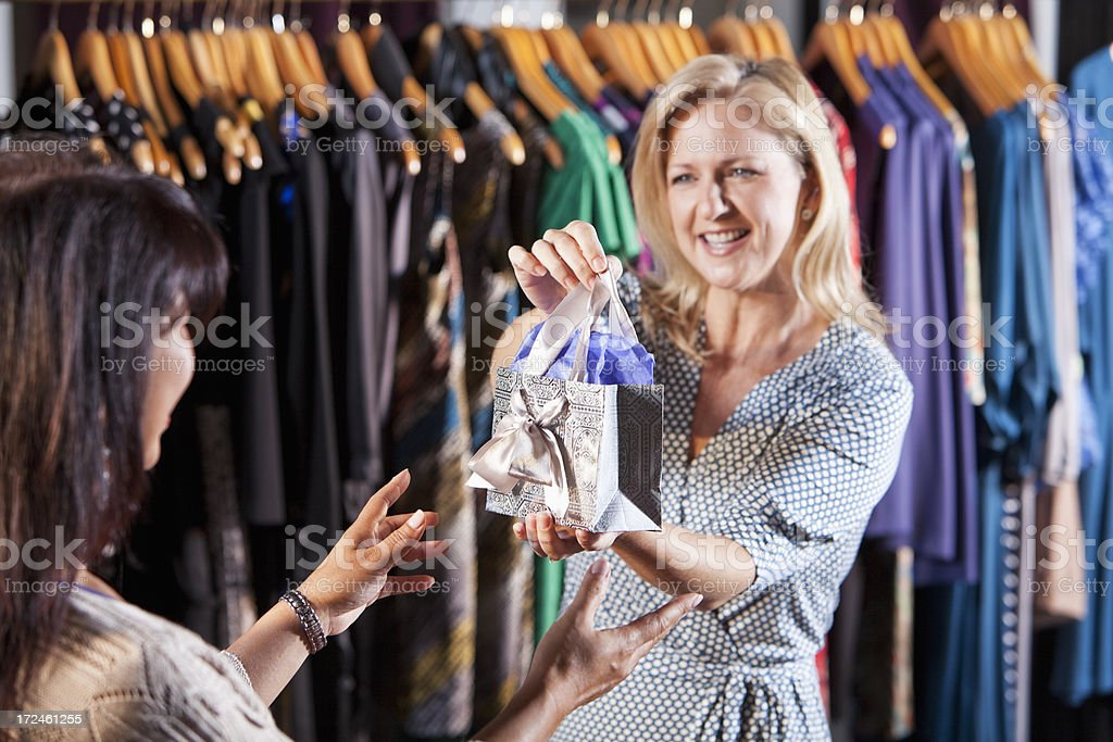 Saleswoman handing customer a gift bag stock photo