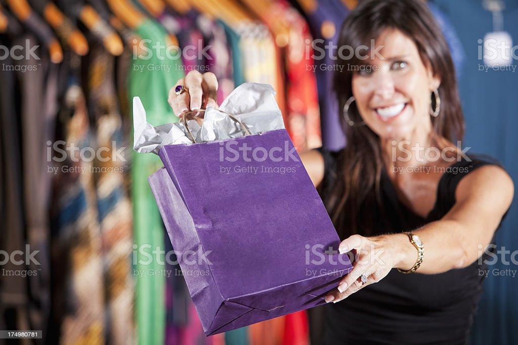 Saleswoman handing customer a shopping bag stock photo