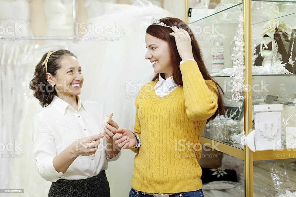 saleswoman helps bride chooses bridal accessories royalty-free stock photo