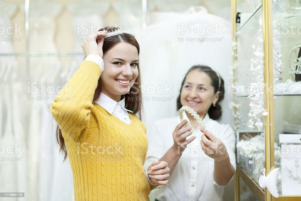 saleswoman helps bride chooses bridal diadem royalty-free stock photo