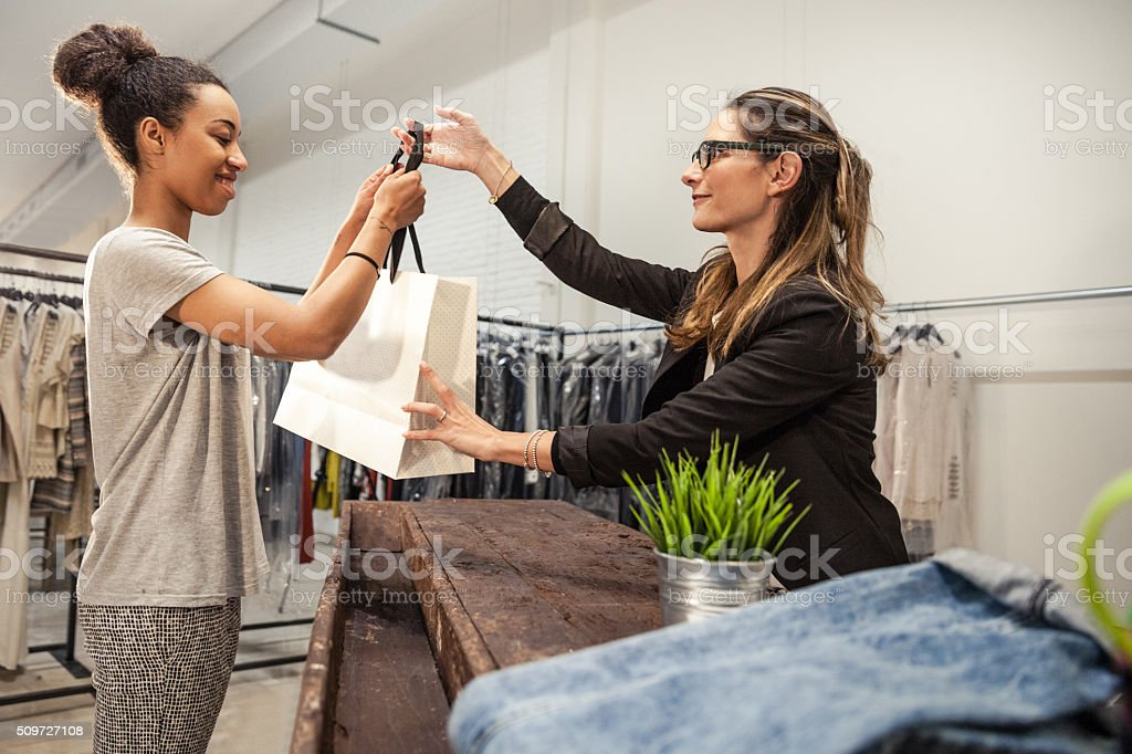 Saleswoman helps customer to choose the right one stock photo
