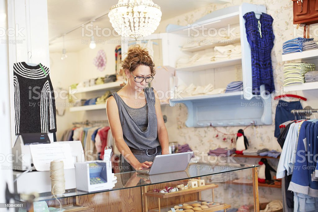 A saleswoman in a boutique working on a laptop stock photo