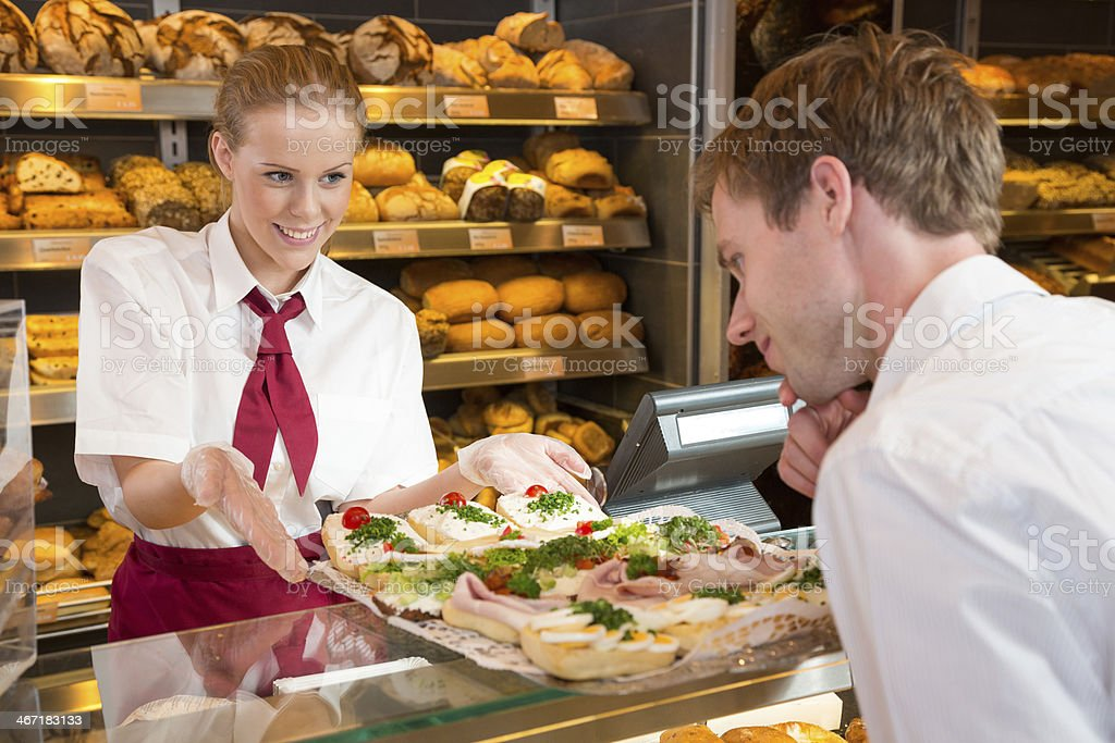 Saleswoman in bakery presenting sandwiches to customer stock photo