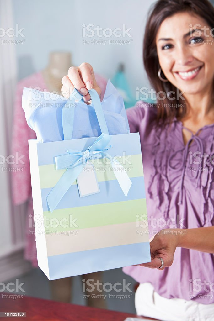 Saleswoman in boutique with shopping bag stock photo