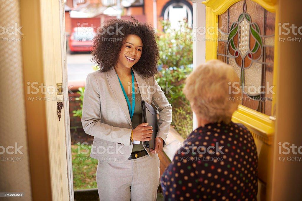 Saleswoman introduces herself to senior woman at the door stock photo