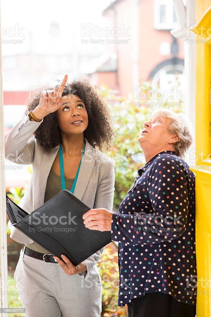 saleswoman or tradeswoman pointing out work to householder stock photo