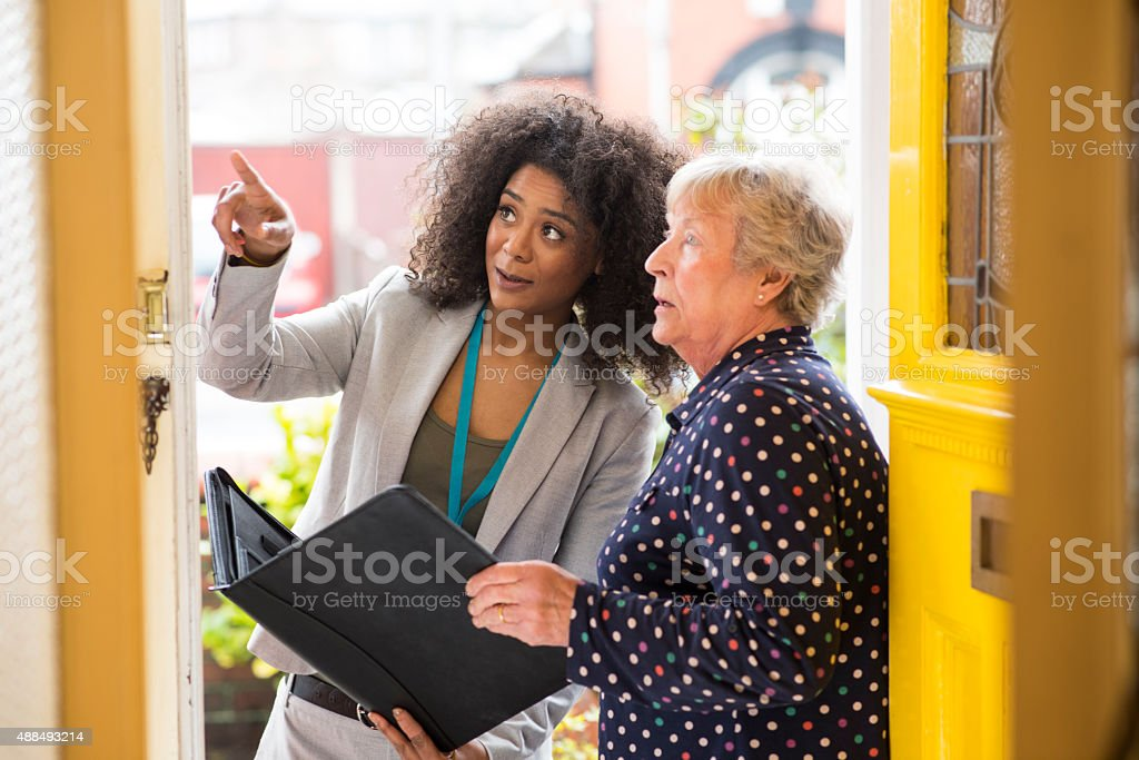 saleswoman  pointing out work to householder stock photo