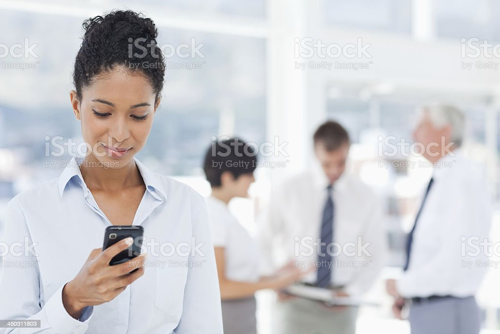 Saleswoman reading text message with colleagues behind her stock photo