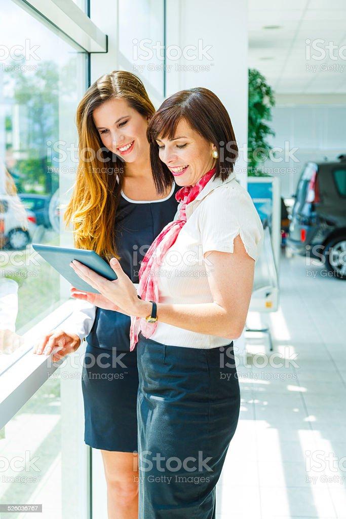 Saleswoman selling car to woman stock photo