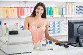 Saleswoman Standing At Cash Register In Supermarket