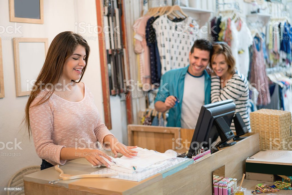 Saleswoman wrapping up clothes at a clothing store stock photo