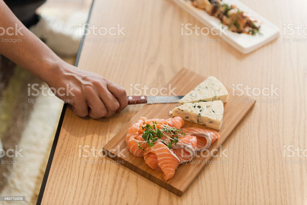 Salmon and cheese dishes were piled in wooden plate stock photo