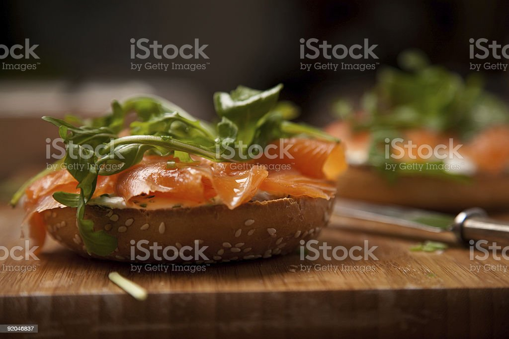 Salmon and rocket bagel on a chopping board stock photo