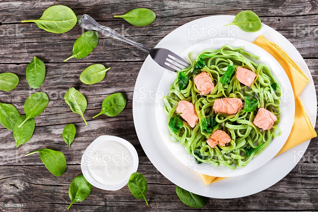 Salmon and Spinach Fettuccine pasta on white dishes stock photo