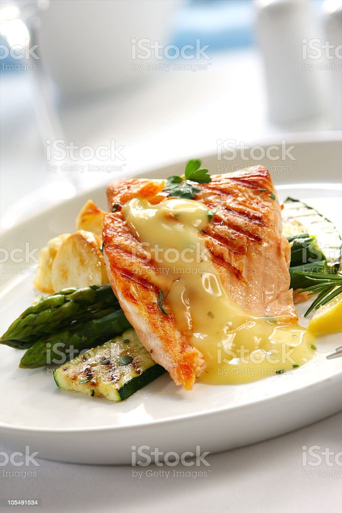 Salmon and vegetables on a white plate stock photo