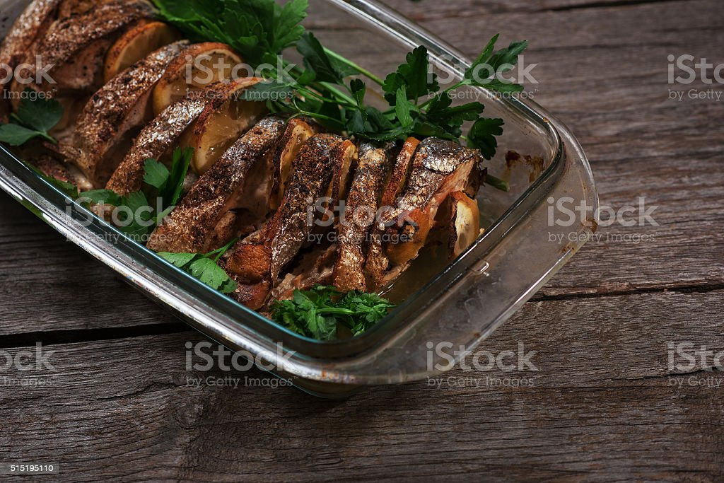 Salmon baked in the oven with lemon and fresh herbs stock photo