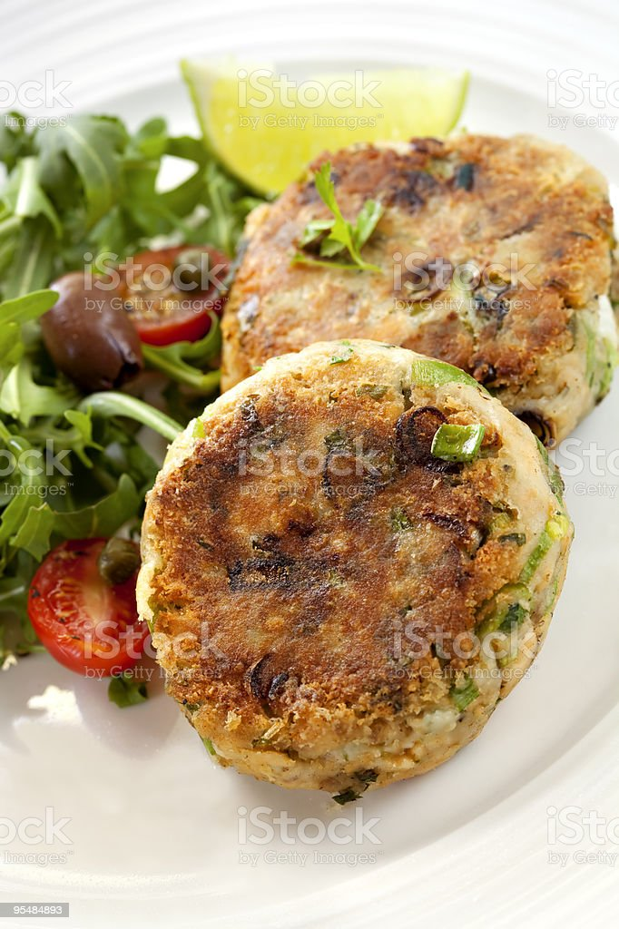 Salmon cakes plates with a fresh salad stock photo