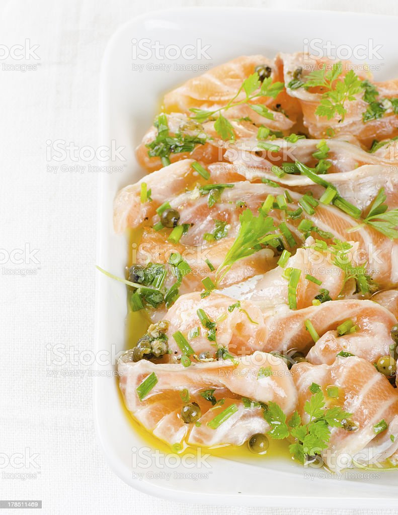Salmon carpaccio - fresh fish slices in marinade royalty-free stock photo