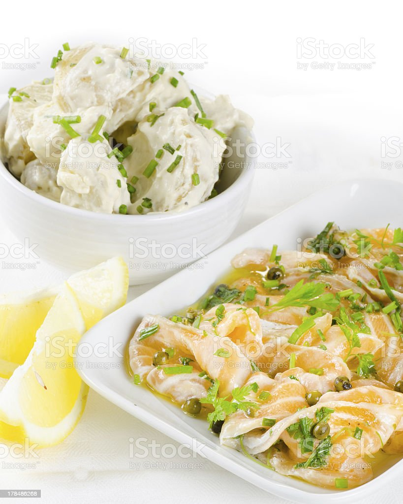 Salmon carpaccio with potato salad and lemon on white royalty-free stock photo