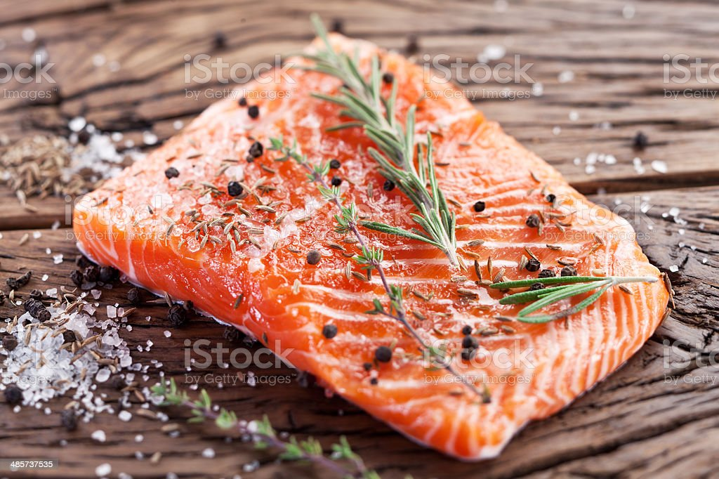 Salmon filet on a wooden carving board. stock photo