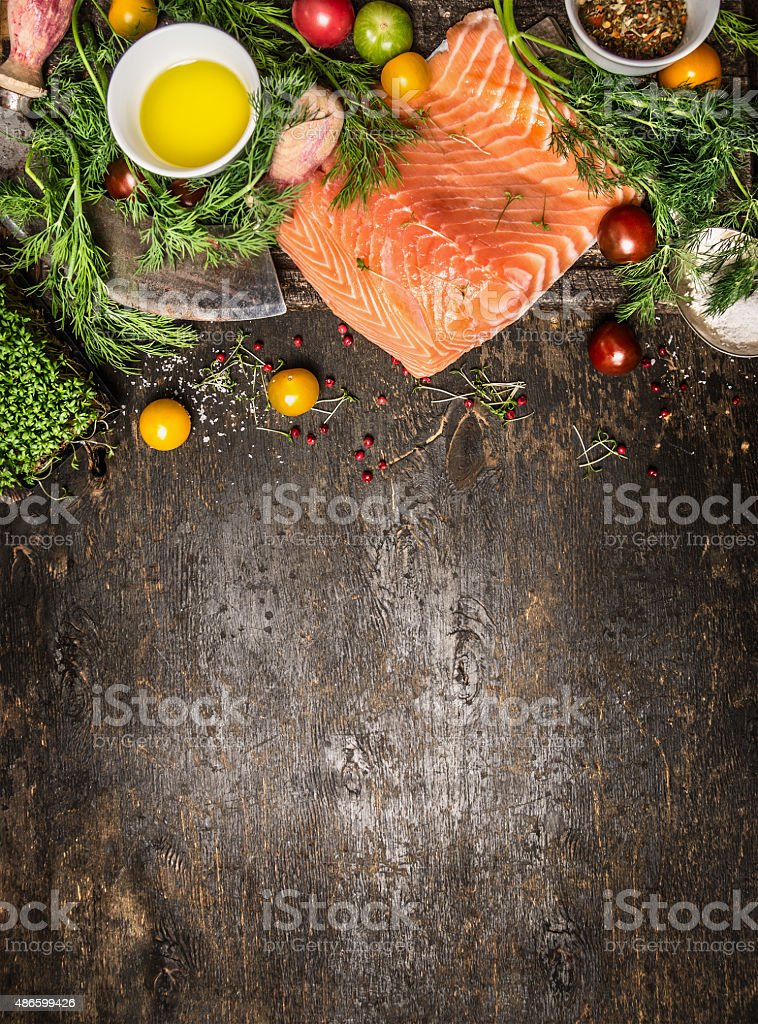 Salmon fillet and ingredients for cooking, wooden background stock photo