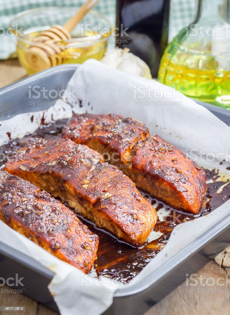 Salmon fillet with balsamic-honey sauce in baking dish, baked stock photo