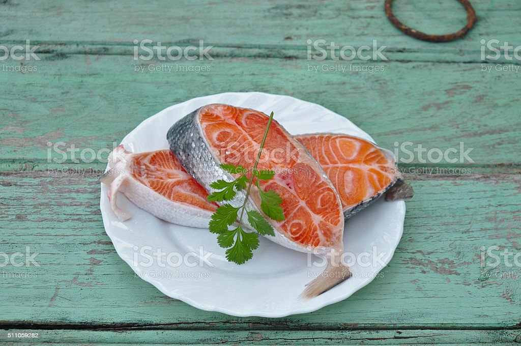 Salmon fillets on an old wooden background with coriander stock photo